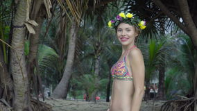 Sensual woman wearing colourful swimwear and wreath on a beautiful summer day between palm trees stock video