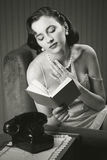 Sensual woman reading a book on armchair Stock Photo