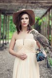 Sensual woman wearing peach color dress and brown hat with bird, outdoor fashion portrait.  stock photo