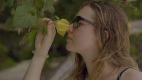 Sensual woman wearing sunglasess smelling flower over tropical plants background. Travel asia concept. Sensual woman wearing sunglasess smelling flower over stock video footage