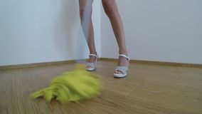 Woman on high heels washes the parquet floor with the yellow mop stock video footage