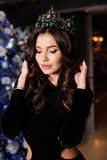 Sensual woman wears elegant dress, posing beside decorated Christmas tree Stock Photo