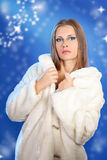 Sensual woman in a white fur on blue background winter fashion p Stock Photography