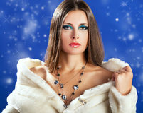 Sensual woman in white fur on blue winter background with snow Stock Image