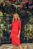 Sensual Woman With Blond Hair In Elegant Dress Posing Near Roses Bushes Royalty Free Stock Photos