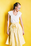 Sensual woman in yellow skirt looking down Royalty Free Stock Photos