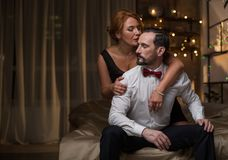 Passionate loving couple cuddling on bed. Sensual women is hugging men with desire. They are sitting in bedroom while celebrating special occasion in the evening Royalty Free Stock Photography