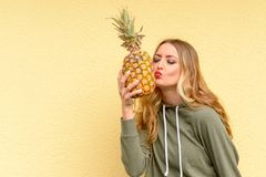 Sensual young blond woman with red lips. Leaning over to kiss a ripe pineapple she is holding in her hand and closed eyes with copy space Royalty Free Stock Image