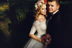 Sensual young blonde bride in white dress hugging romantic groom Stock Photo