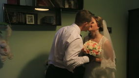 Sensual young bride and groom softly kissing in evening luxury hotel room stock footage