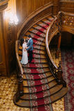 Sensual young bride and handsome elegant groom posing on old stairs with the background of amazing wooden vintage Royalty Free Stock Image