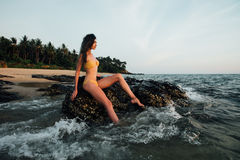 Sensual young brunette beauty wearing yellow swimsuit with beautiful hair sitting on stone at the beach. Over beautiful sea and poses , sky and tropical island Stock Images