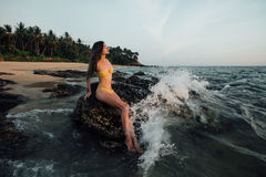 Sensual young brunette beauty wearing yellow swimsuit with beautiful hair sitting on stone at the beach. Over beautiful sea and poses , sky and tropical island Stock Photography