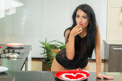 Sensual young brunette girl eating strawberry with Royalty Free Stock Photo