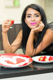 Sensual young brunette girl eating strawberry with Stock Image
