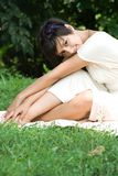 Sensual young brunette sitting on grass. Young girl enjoying her free time sitting on green grass ourdoors Stock Images