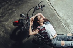 Sensual young brunette woman posing on motorcycle. High angle view of sensual young brunette woman posing on motorcycle Stock Image