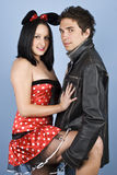 Sensual  young couple. Beautiful young couple,the woman it is dressed in mouse outfit and man in leather jacket and standing  in a sensual position  holding her Stock Photo