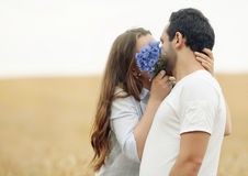 Sensual young couple hiding a kiss behindthe flowers Stock Photos