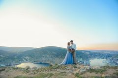 Sensual young couple in love standing on the rock in the sea near the beach with big cliffs. Man and woman holding hands stock images