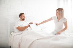 Sensual young couple together in bed. Angry couple in bedroom on a white background. The couple in love quarreled. A bearded men and blonde girl insult each Royalty Free Stock Photos