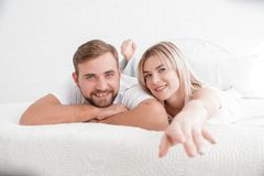 Sensual young couple together in bed. Happy couple in bedroom  on a white background. Young loving couple hugging each other, smiling and posing on camera on Royalty Free Stock Images