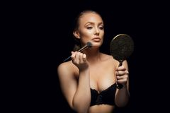 Sensual young female putting on make up Royalty Free Stock Photography