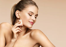 Sensual Young Girl Applying Foundation On Her Face Using Makeup Sponge. Stock Images