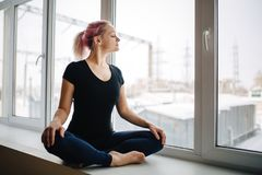 Sensual young girl with pink hair is meditating while sitting in lotus position near window. Her eyes are closed with peace and pl. Easure royalty free stock photo