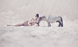 Sensual young lady playing with the pony Stock Image