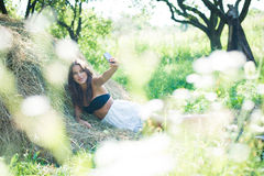 Sensual young lady relaxing at hay taking selfy Stock Photo