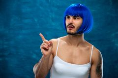 Young male cross dressing person wearing blue wig. Sensual young male cross dressing person wearing blue wig and female cloth showing something useful on blank Stock Photography
