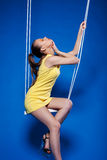 Sensual young model with UV makeup posing on swing Royalty Free Stock Images