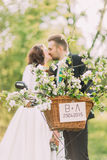 Sensual young newlywed couple kiss. Park outdoors. Focus on decorated bicycle basket Stock Photography