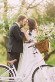 Sensual young newlywed couple posing in park. White bicycle in foreground Stock Photos