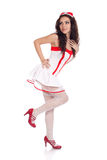 Sensual young nurse looking aside. Full body shot of a sexy beautiful young nurse wearing red high heels shoes looking aside on isolated white background. High Stock Photo