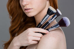 Sensual young rehead woman with set of makeup brushes. Closeup of sensual young rehead woman with set of makeup brushes over grey background Stock Images