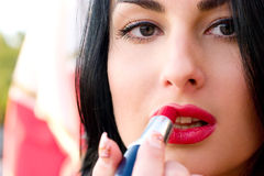Sensual young woman applying cosmetics. On her lips Royalty Free Stock Image