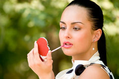Sensual young woman applying cosmetics on her lips Stock Photo