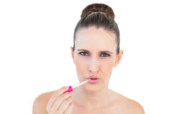 Sensual young woman applying lip gloss Royalty Free Stock Photography