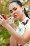 Sensual young woman applying lipstick Stock Images