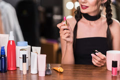 Sensual young woman applying lipstick backstage. Voluptuous girl is doing make-up in dressing room. She is sitting at desk near other cosmetology. Focus on pink Stock Images