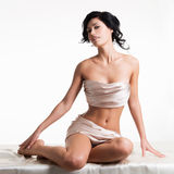 Sensual young woman with beautiful body in the beige silk Royalty Free Stock Image