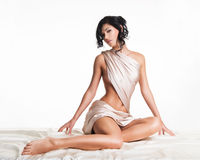 Sensual young woman with beautiful body in the beige silk Stock Images
