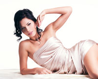 Sensual young woman with beautiful body in the beige silk Royalty Free Stock Photo