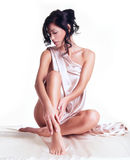 Sensual young woman with beautiful body in the beige silk Royalty Free Stock Photography