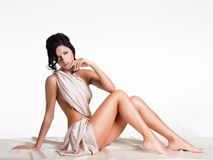 Sensual young woman with beautiful body in the beige silk Stock Image