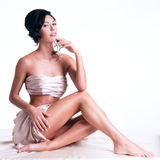 Sensual young woman with beautiful body in the beige silk Royalty Free Stock Photos