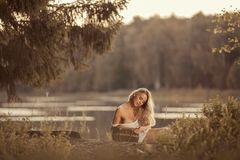 Sensual young woman with beautiful breasts sitting and holding picnic basket. Lovely young woman with beautiful breasts sitting by the lake at sunset and holding