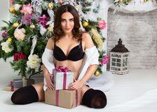 Sensual young woman in black lingerie near  Christmas tree holding gift box. Christmas morning. Nude sexy girl in a white shirt in Stock Images